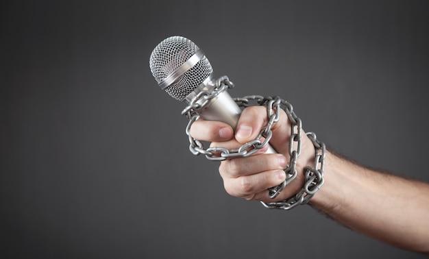 Microfono umano della tenuta della mano legato con le catene