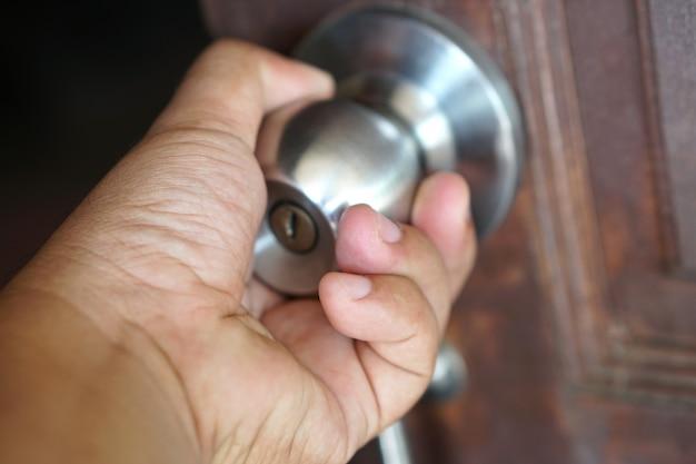 La mano umana sta aprendo la porta della stanza