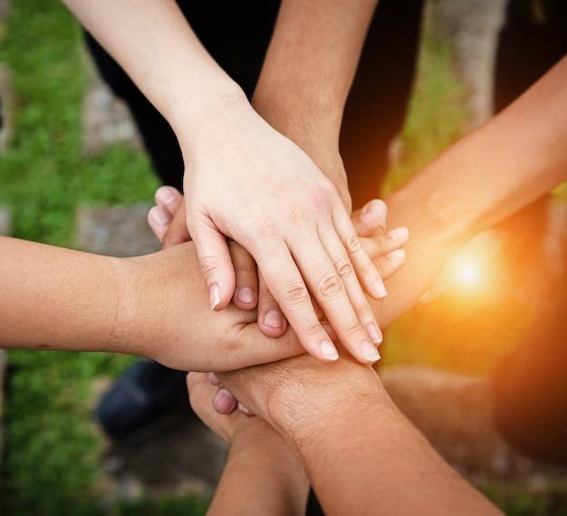 La mano umana sta toccando insieme, per potere e successo, concetto di lavoro di squadra