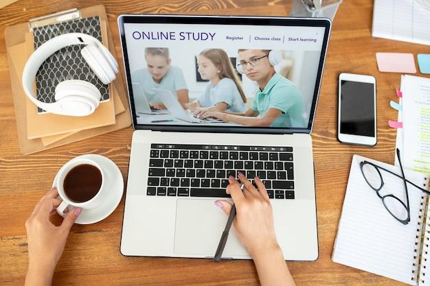 Mano umana sulla tastiera del laptop che naviga sul sito web di apprendimento a distanza mentre è seduto alla scrivania a casa