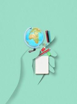 Mano umana fatta di carta che tiene accessori e oggetti per studiare, viaggiare, scrivere su sfondo verde. collage d'arte luminoso colorato e concettuale contemporaneo, mockup con copyspace.