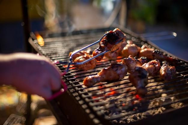 Una mano umana gira le cosce di pollo su un barbecue con pinze per grigliare. cucinare il cibo su un fuoco aperto la sera. festa in cortile