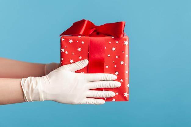 Mano umana in guanti chirurgici bianchi che tengono scatola regalo rossa. concetto di condivisione, donazione o consegna.
