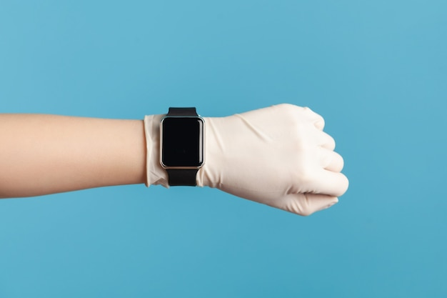 Mano umana in guanti chirurgici bianchi che tengono e mostrano lo schermo dell'orologio intelligente.