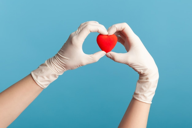 Mano umana in guanti chirurgici bianchi che tengono in mano una piccola forma di cuore rosso.