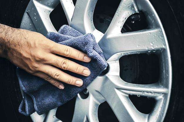 La mano umana pulisce il cerchio in lega dell'auto con un panno in microfibra da vicino