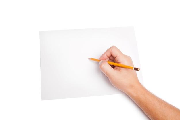 Mano umana con la matita che scrive qualcosa su bianco