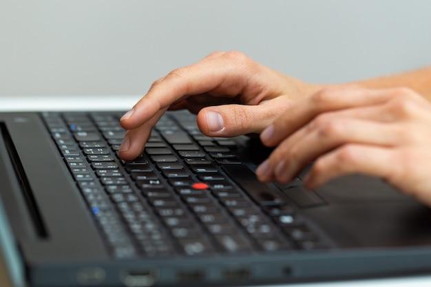 Scrittura della mano umana sul computer portatile in ufficio da vicino