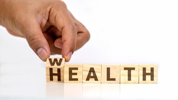 Le mani umane stanno trasformando il messaggio sui blocchi di legno da salute a ricchezza, idee di assistenza sanitaria e un futuro finanziario sostenibile.