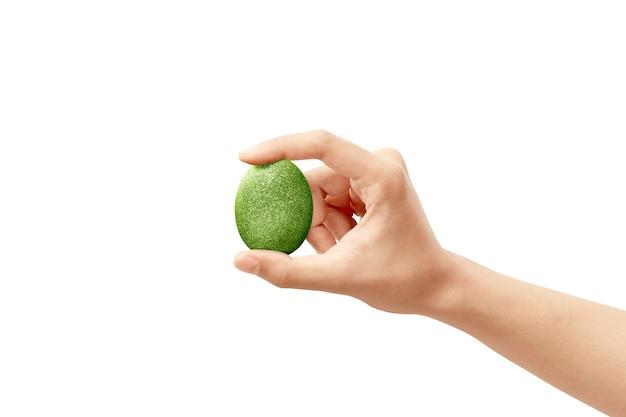 Mani umane che tengono le uova di pasqua verdi isolate. buona pasqua