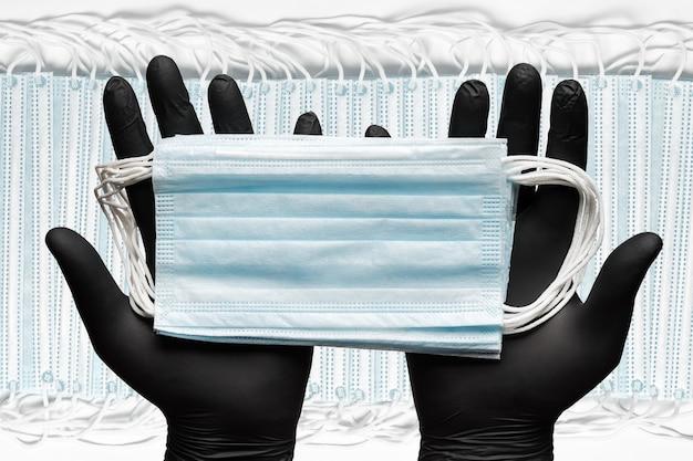 Mani umane che tengono la maschera chirurgica medica in due guanti protettivi neri sullo sfondo di un sacco di bende respiratorie per il viso umano con cinturini per le orecchie in gomma. concetto medicinale igiene e assistenza sanitaria.