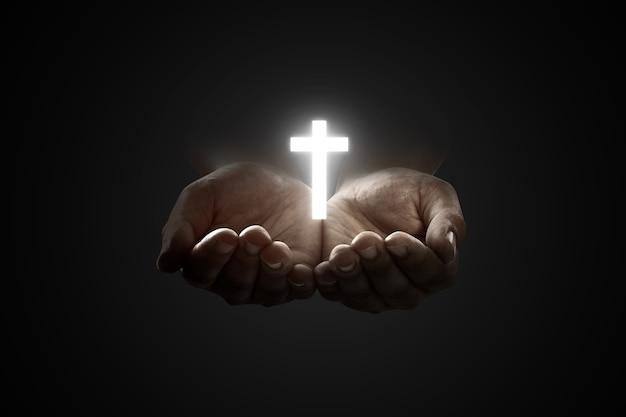 Mani umane in preghiera a dio con croce cristiana lucida su sfondo nero