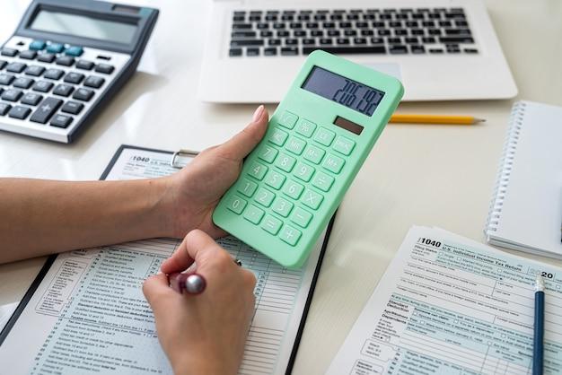 Mani umane con il primo piano del modulo fiscale 1040. concetto di tassazione