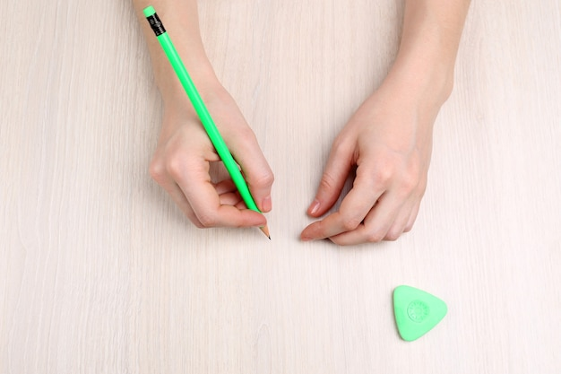 Mani umane con matita e gomma cancellabile su tavola di legno