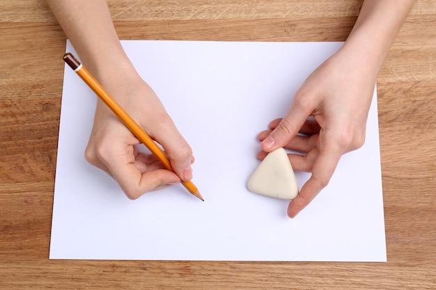 Mani umane con scrittura a matita su carta e gomma per cancellare sul tavolo di legno