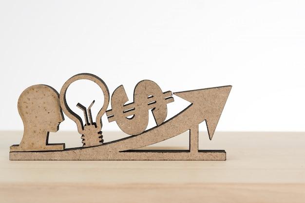 Testa umana, lampadina, segno di dollaro e segno di freccia sulla tavola di legno