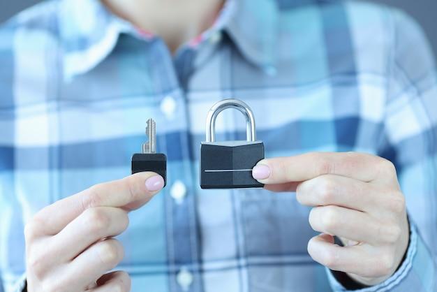 L'uomo tiene la chiave e il lucchetto sulla sua mano. assicurazione sulla proprietà contro il concetto di sovvenzioni