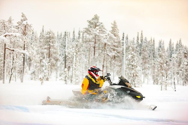 Umano in tuta e casco alla guida di una motoslitta vicino alla neve profonda all'aperto nella foresta