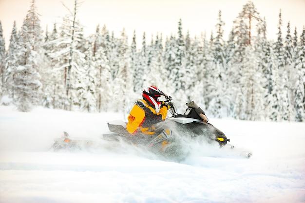 Umano nel vestito di un corridore che guida una motoslitta vicino alla superficie della neve profonda all'aperto
