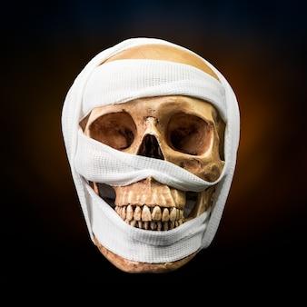 Cranio umano legato con benda su sfondo scuro