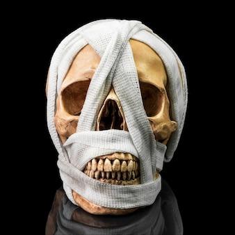 Legame del cranio umano con benda sporca su oscurità