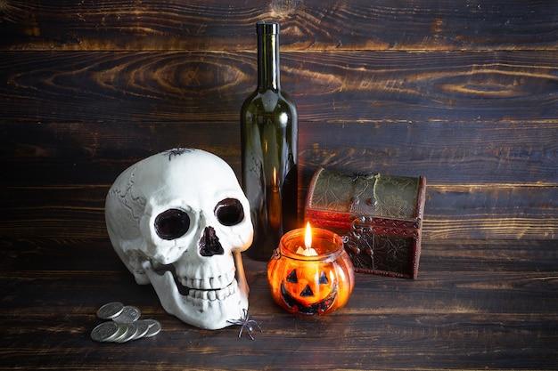 Cranio umano, bottiglia, monete, cofanetto e candela accesa, forma di candeliere di zucca su superficie di legno