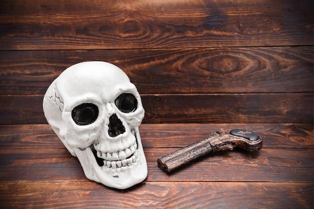 Cranio umano e pistola scolpita vintage sulla superficie della plancia di legno.