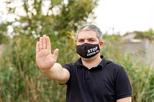 Umano che indossa una maschera tendendo la mano per fermare il virus covid-19