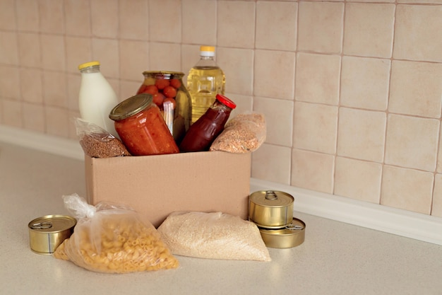 Assistenza umanitaria durante una pandemia. scatola con ingredienti essenziali, pasta, cereali e frutta