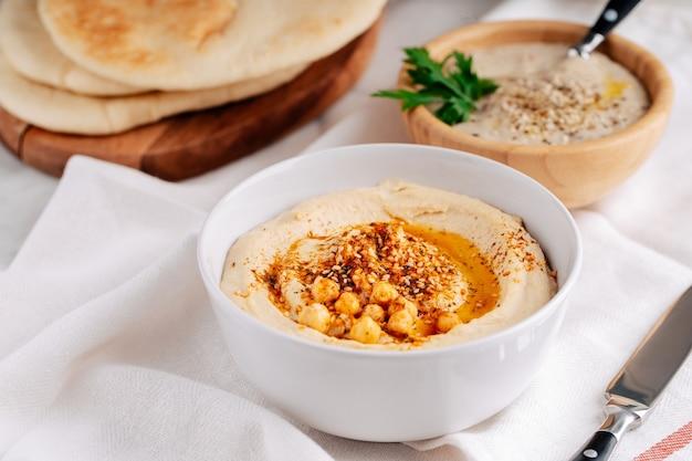 Hummus e baba ghanoush in una ciotola e pane pita su sfondo chiaro.