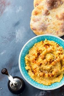 Hummus, ceci, con spezie e pita, focaccia in un piatto su una superficie di pietra grigia