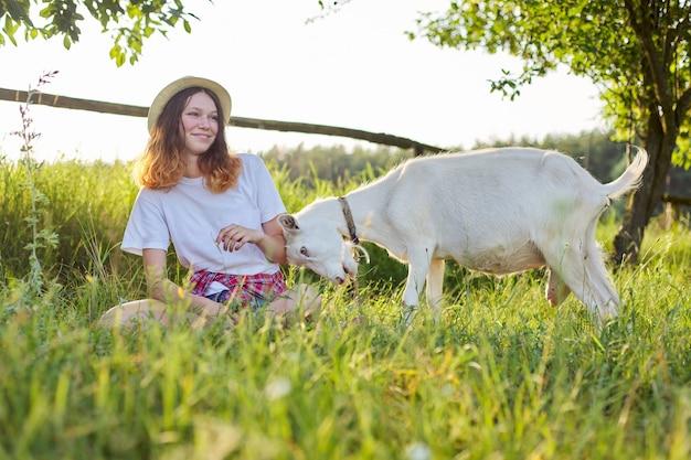 Umorismo, ragazza dell'adolescente di intestazione della capra dell'azienda agricola domestica bianca