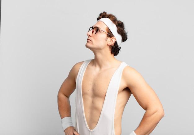 Uomo sportivo umoristico che si sente confuso o pieno o dubbi e domande, chiedendosi, con le mani sui fianchi, vista posteriore