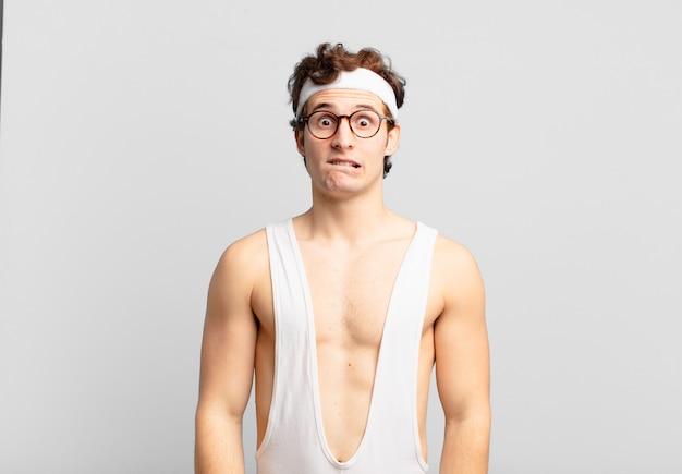 Uomo sportivo umoristico che sembra perplesso e confuso, mordendosi il labbro con un gesto nervoso, non conoscendo la risposta al problema