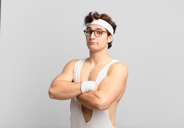 Uomo sportivo umoristico che scrolla le spalle, si sente confuso e incerto, dubitando con le braccia incrociate e lo sguardo perplesso