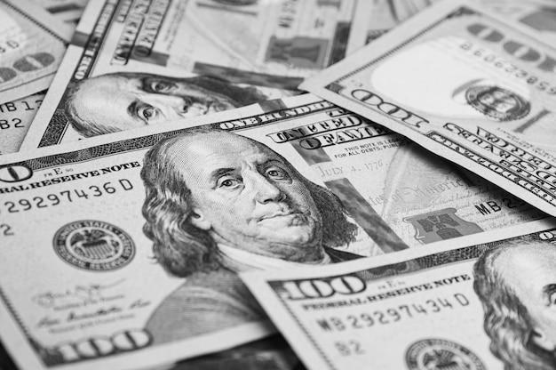 Un centinaio di banconote americane sono sparse. banconote da cento dollari in contanti, immagine di sfondo del dollaro.