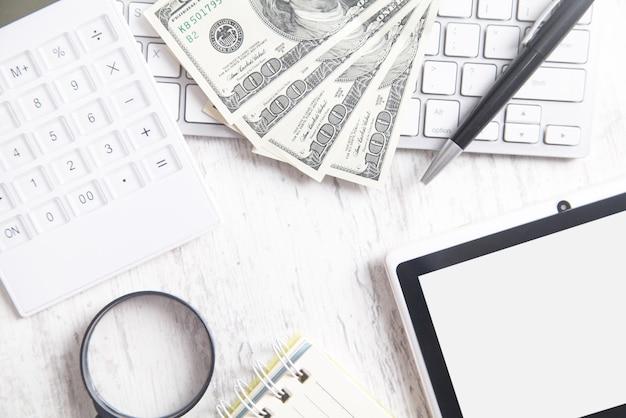 Banconote da cento dollari con una tastiera di computer, tablet e calcolatrice. vista dall'alto