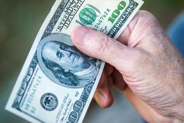 Banconota da cento dollari in mano dell'uomo anziano, primo piano