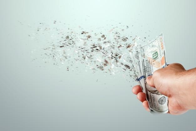 Le banconote da cento dollari volano in polvere nella mano di un uomo. perdite di denaro, grosse spese, prestiti, mutui.