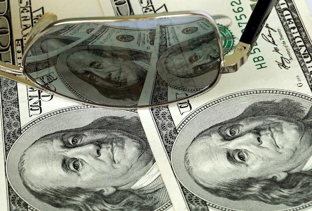 Banconote da cento dollari in riflesso di punti a specchio