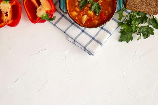 Gulasch ungherese in un piatto di ceramica pane paprika prezzemolo mangiare sano un alimento ricco di vitamine e fibre vista dall'alto con spazio di copia