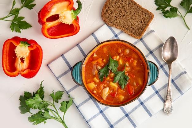 Gulasch ungherese in un piatto di ceramica pane paprika prezzemolo su un tavolo bianco vista dall'alto cibo sano ricco di vitamine antiossidanti e fibre