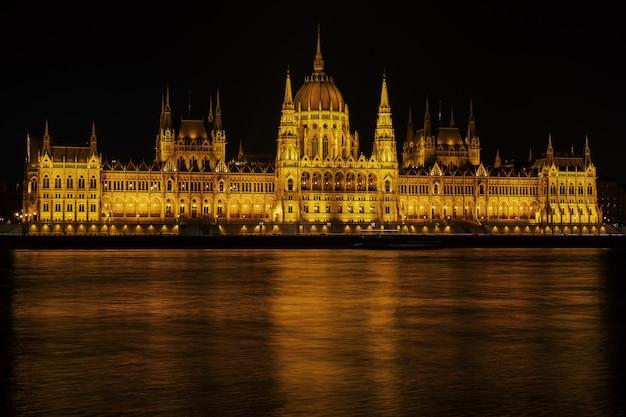 Vista ungherese di notte della costruzione del parlamento dall'argine del danubio