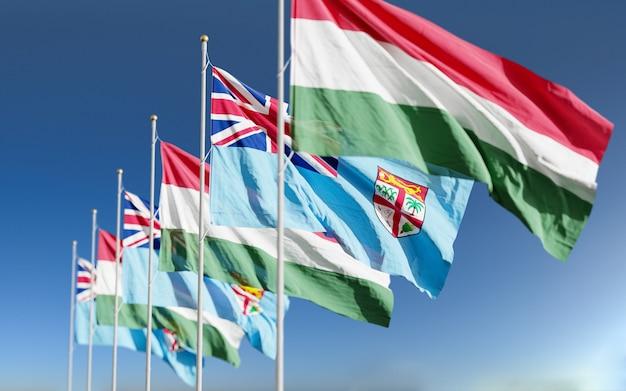 Bandiere dell'ungheria fiji che ondeggiano al fondo del cielo
