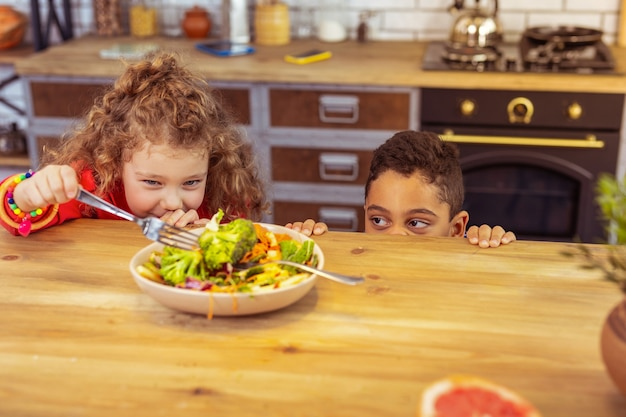 Non affamato. bella ragazza bionda che tiene la forchetta nella mano destra e guarda le verdure