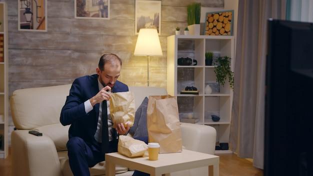Uomo d'affari affamato in tuta che arriva a casa con cibo in un sacchetto di carta.