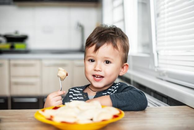 Bambino affamato che mangia gnocchi in cucina, seduto al tavolo con una giacca grigia