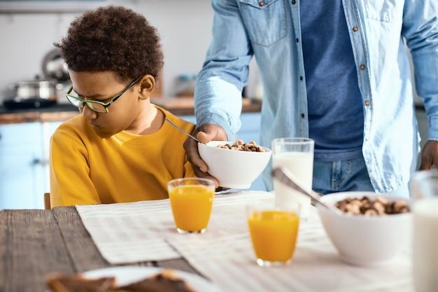 Non affamato. simpatico ragazzo pre-adolescente che distoglie la faccia da suo padre che gli dà una ciotola di cereali, esprimendo la sua riluttanza a mangiare