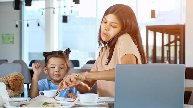 La figlia affamata chiede alla mamma di darsi da mangiare al ristorante. la mamma asiatica della donna d'affari dà una fetta di pizza al bambino seduto al tavolo con il tè e il primo piano grigio del computer portatile