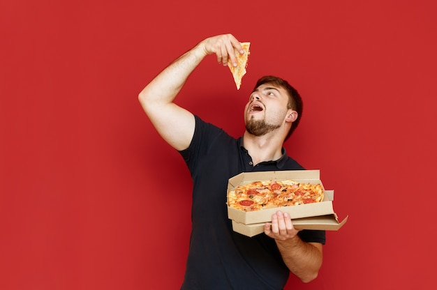 Uomo divertente affamato si alza e prende una fetta di pizza fuori dalla scatola